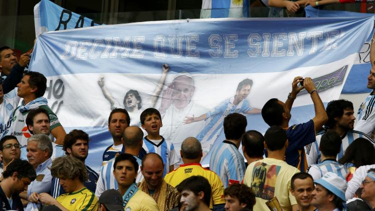 "Fans hold up banner with pictures of Maradona, Pope Francis and Argentina's Lionel Messi that reads ""tell me how it feels!"" in Porto Alegre"