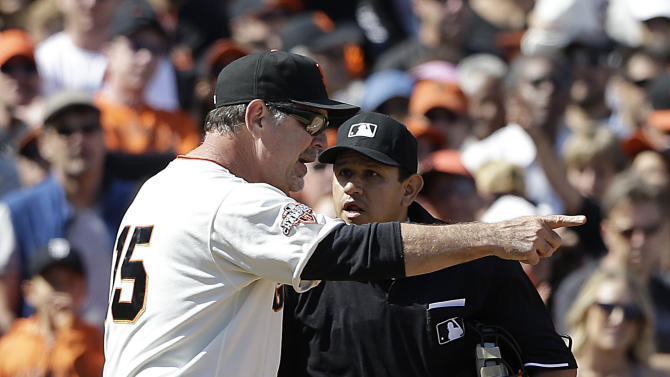 San Francisco Giants manager Bruce Bochy, left, argues with umpire Alfonso Marquez after Buster Posey was called out at third base during the eighth inning of a baseball game against the Colorado Rockies in San Francisco, Saturday, May 25, 2013. Bochy was ejected by Marquez. (AP Photo/Jeff Chiu)