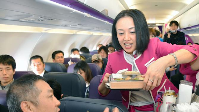 In this March 1, 2012 photo, a passenger buys a meal during the first flight by Peach Aviaction from Osaka, western Japan, bound for Sapporo, northern Japan. Japan has a reputation for loving expensive things like overpriced real estate, gourmet melons and luxury brands. But the nation is finally discovering the joy of flying cheap, with the arrival this year of three low-cost carriers. The takeoff of AirAsia Japan, Peach Aviation and Jetstar Japan could change lifestyles. (AP Photo/Kyodo News) JAPAN OUT, MANDATORY CREDIT, NO LICENSING IN CHINA, FRANCE, HONG KONG, JAPAN AND SOUTH KOREA
