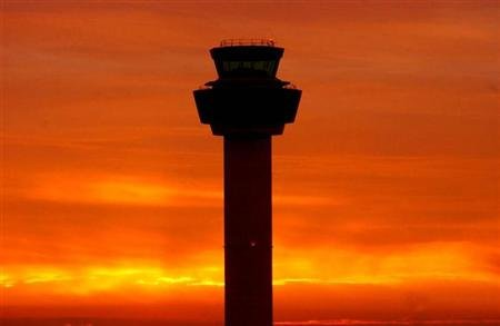 The sun sets behind the control tower at Stansted Airport in Essex, southern England, December 16, 2003 file photo. REUTERS/Rowan Griffiths MD/JV
