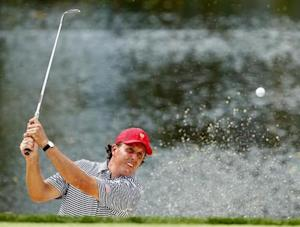 U.S. golfer Phil Mickelson hits from a sand trap on the third hole during the Foursome matches for the 2013 Presidents Cup golf tournament at Muirfield Village Golf Club in Dublin, Ohio