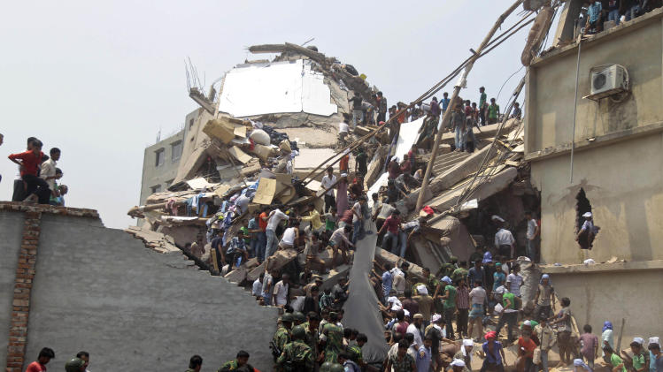 Rescue workers and people look for survivors after an eight-story building housing several garment factories collapsed in Savar, near Dhaka, Bangladesh, Wednesday, April 24, 2013. Dozens were killed and many more are feared trapped in the rubble. (AP Photo/ A.M. Ahad)