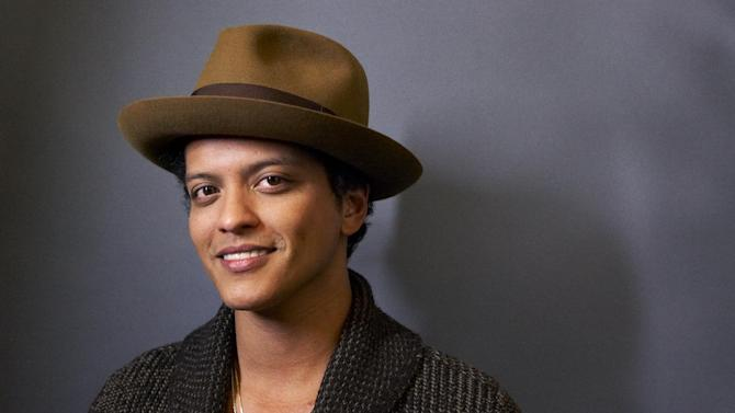 """FILE - This Nov. 5, 2012 file photo shows American performer Bruno Mars posing for a portrait in New York. WEtv announced Wednesday, April 10, 2013, that Grammy winner's four sisters will appear in a reality series documenting the recording process of their debut album. """"The Lylas"""" will include Tiara, Tahiti and Presley, who are moving from Hawaii to Los Angeles to join older sister Jamie. (Photo by Dan Hallman/Invision/AP, file)"""