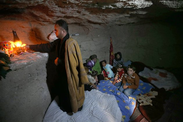 A defected Syrian policeman, Adnan al-Hamod, 33, lights a kerosene lamp inside an underground shelter he made using a jackhammer to protect his family from Syrian government forces shelling and airstrikes, at Jirjanaz village, in Idlib province, Syria, Thursday, Feb. 28, 2013. Across northern Syria, rebels, soldiers, and civilians are making use of the country's wealth of ancient and medieval antiquities to protect themselves from Syria's two-year-old war. They are built of thick stone that has already withstood centuries, and are often located in strategic locations overlooking towns and roads. (AP Photo/Hussein Malla)