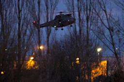 A helicopter flies over a building, where…