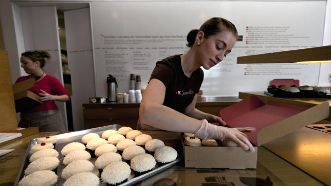 "In this photo taken Monday, March 5, 2012, Sprinkles Cupcakes Sara Cebulski, right, arranges a custom box of cupcakes at Sprinkles in Beverly Hills, Calif. A new 24-Hour Cupcake ""ATM,"" an automatic machine that will be continuously restocked to dispense fresh cupcakes is opening at Sprinkles Cupcakes. (AP Photo/Damian Dovarganes)"