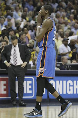 Oklahoma City Thunder's Kevin Durant holds his head as he walks from the floor in a timeout during overtime of Game 4 in a Western Conference semifinal NBA basketball playoff series against the Memphis Grizzlies as Scott Brooks looks down in Memphis, Tenn., Monday, May 13, 2013. The Grizzlies defeated the Thunder 103-97 in overtime(AP Photo/Danny Johnston)