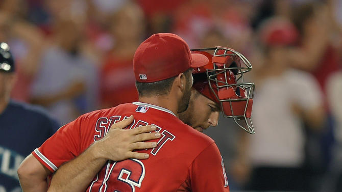 Los Angeles Angels relief pitcher Huston Street, left, and catcher Chris Iannetta congratulate each other after they defeated the Seattle Mariners 5-0 in a baseball game, Wednesday Sept. 17, 2014, in Anaheim, Calif. (AP Photo/Mark J. Terrill)