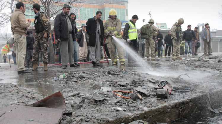An Afghan firefighter man washes the scene of a suicide attack in Kabul, Afghanistan, Wednesday, Feb. 27, 2013. A man wearing a black overcoat and carrying an umbrella as a shelter against the heavy snow crossed a street in the Afghan capital early Wednesday morning toward an idling bus filled with Afghan soldiers, where he laid down and wiggled underneath. Then he exploded, engulfing the undercarriage of the bus in flames. (AP Photo/Musadeq Sadeq)