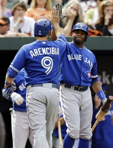 Toronto Blue Jays' J.P. Arencibia, left, high-fives Rajai Davis after scoring a run on a bases-loaded walk in the 11th inning of a baseball game against the Baltimore Orioles, Wednesday, April 24, 2013, in Baltimore. Toronto won 6-5. (AP Photo/Patrick Semansky)