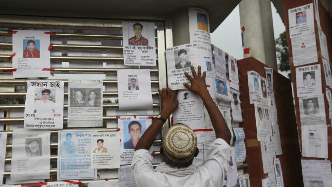A Bangladeshi puts up a picture of his missing relative at a makeshift morgue in a schoolyard near a building that collapsed Wednesday in Savar, near Dhaka, Bangladesh, Saturday, April 27, 2013. Police in Bangladesh arrested two owners of a garment factory in a shoddily-constructed building that collapsed this week, killing hundreds of people, as protests spread to a second city Saturday with hundreds of people throwing stones and setting fire to vehicles. (AP Photo/Kevin Frayer)
