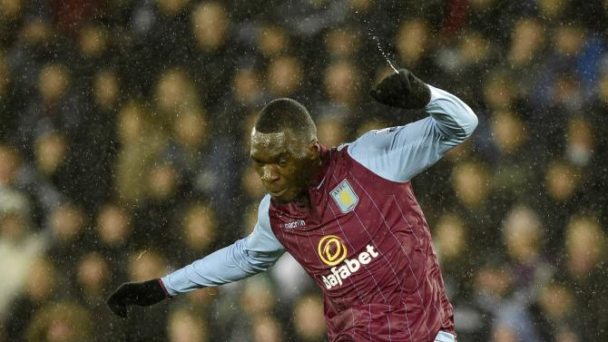 Aston Villa's Christian Benteke takes a free kick in the pouring rain during their English Premier League soccer match at the Liberty Stadium in Swansea
