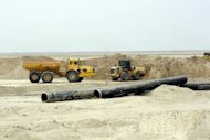 Metal pipes are seen as the land is cleared from ordnance and mines laid down during the 1980-1988 Iraq-Iran war in the massive Majnoon oil field in southeastern Iraq in February 2012. Iraq's oil output now stands at 3.2 million barrels per day, outpacing neighbouring Iran to become the second-biggest producer in OPEC, Iraq's top energy official said on Sunday