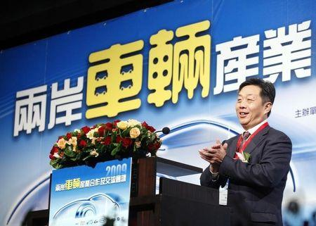 Dong, Secretary General of the China Association of Automobile Manufacturers, claps while speaking at the cross strait automobile conference in Taipei