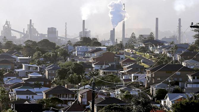 In this Wednesday, July 2, 2014 photo, smoke billows out of a chiming chimney stack of a steel works factories in Port Kembla 86 kilometers (53 miles) south of Sydney. The Senate is expected to vote as early as Monday, July 7, 2014, to repeal an unpopular, two-year-old tax charged to around 300 of the country's biggest carbon polluters. (AP Photo/Rob Griffith)