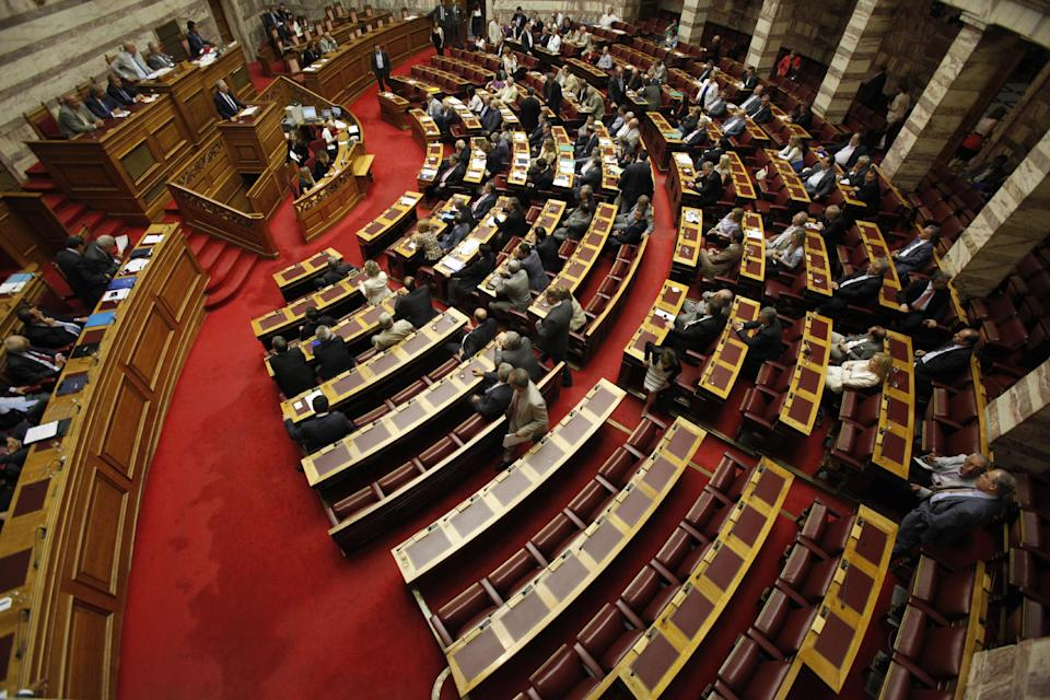 Seats of lawmakers of the extreme right-wing Golden Dawn party are seen empty after parties' lawmakers and leader  Nikolaos Michaloliakos left the parliament hall following the left parties' lawmakers exit during Michaloliakos speech at the Parliament in Athens, Saturday, July 7, 2012. (AP Photo/Kostas Tsironis)