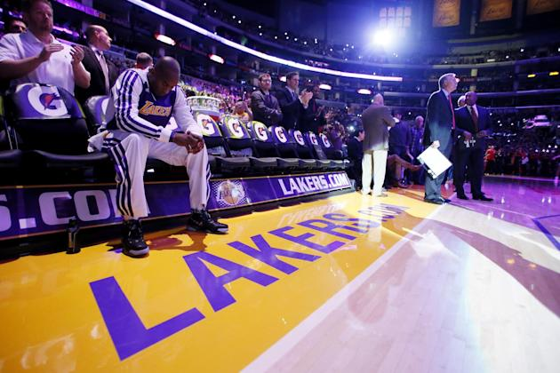 Los Angeles Lakers' Kobe Bryant sits on the bench, he is the last player to be introduced to the crowd, as head coach Mike D'Antoni, right, looks on before the NBA basketball game against the