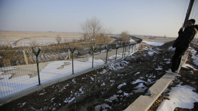 In this Feb. 6, 2013 photo, a Chinese tourist looks at a newly erected border fence in Dandong, China, opposite the North Korean border town of Sinuiju. China's patience with North Korea is wearing thin, and a widely-expected nuclear weapons test by the latter could bring that frustration to a head. Beijing signaled its growing unhappiness by agreeing to tightened U.N. sanctions after North Korea launched a rocket in December, eliciting harsh criticism from Pyongyang and comment from China watchers surprised by Beijing's unusually tough line. (AP Photo/Eugene Hoshiko)
