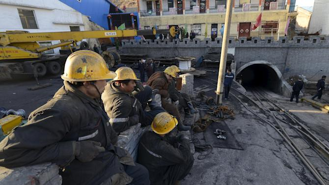 Rescuers sit next to the entrance of a coal mine after a flooding incident in Datong
