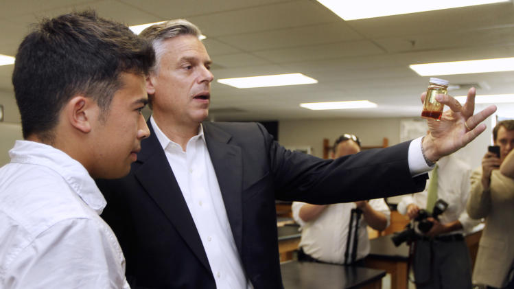 Republican presidential candidate, former Utah Gov. Jon Huntsman examines a jar of bio diesel fuel made from cooking oil with student Elias Kim during a campaign stop at Merrimack High School, Wednesday, Sept. 14, 2011, in Merrimack, N.H. (AP Photo/Jim Cole)