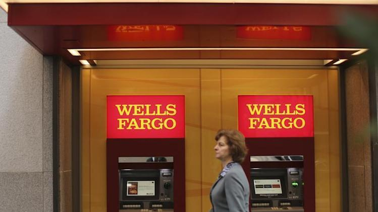 A woman walks past teller machines at a Wells Fargo bank in San Francisco