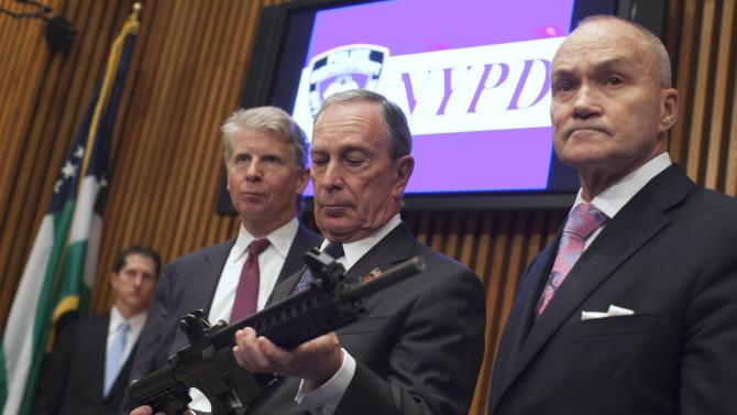 Bloomberg examines a confiscated gun during a 2012 news conference