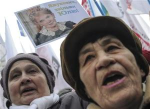 A supporter of jailed former Ukrainian Prime Minister and opposition leader Tymoshenko holds a portrait of her during a rally in front of the Parliament building in Kiev