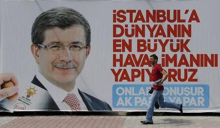 A man runs past by an election billboard with a picture of Turkish Prime Minister Davutoglu is pictured in Istanbul's financial district of Gayrettepe, Turkey
