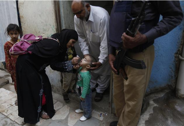 A polio worker administers polio vaccine drops to a boy in Karachi