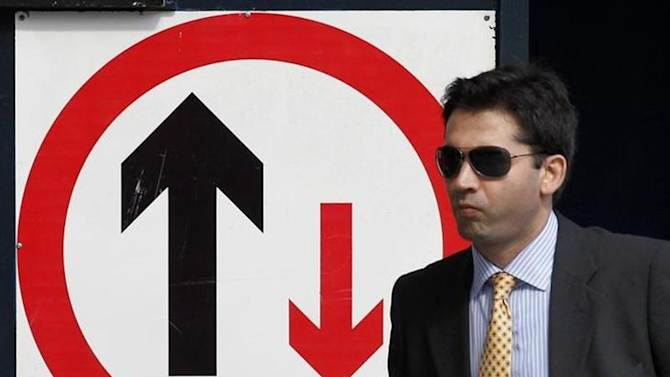 A businessman walks past a sign on a construction site in the financial district of the city of London August 19, 2011.