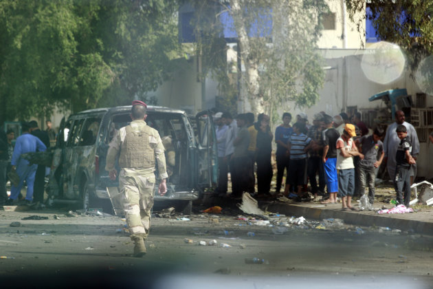 Iraqi security forces and civilians inspect the scene of a car bomb attack in the Kazimiyah area of Baghdad, Iraq, Saturday, June 16, 2012. Car bombs targeting religious processions in Iraq's capital killed and wounded scores of people on the last day of a Shiite pilgrimage already hit three times in some of the deadliest violence since American troops withdrew, police said. (AP Photo/Hadi Mizban)