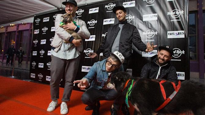 John Baldwin Gourley, Zach Carothers, Kyle O'Quin and Jason Sechrist of Portugal. The Man walk the red carpet with sled dog Duster and puppy Rita at the Grand Opening party of Hard Rock Cafe Anchorage on Fri., Sept. 19, 2014 in Anchorage, Ala. (Photo by Kerry Tasker/Invision for Hard Rock International/AP Images)