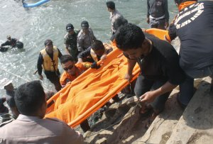 Rescuers carry the body of a victim killed after a …