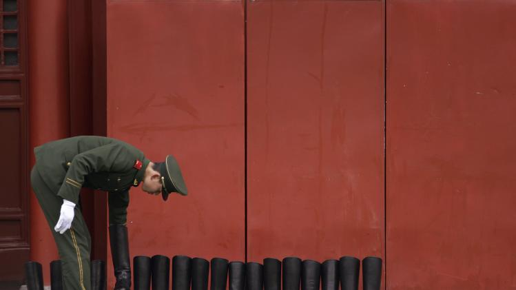 A paramilitary police officer lines up a row of newly-polished soldiers' boots at the Forbidden City compound in Beijing
