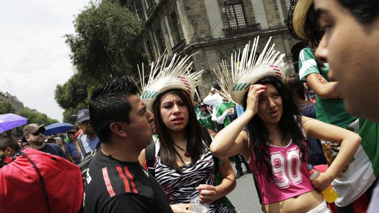Mexico soccer fans react after watching the 2014 World Cup soccer match between Mexico and Netherlands during a public viewing at the Zocalo square in downtown Mexico City