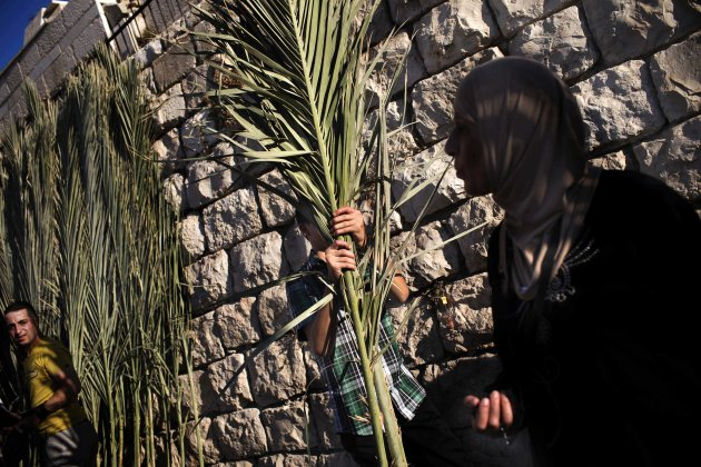 A Palestinian man carries palm fronds to lay on the graves relatives as a tradition during the first day of Eid al-Fitr, which marks the end of the Muslim fasting month of Ramadan, outside Jerusalem's