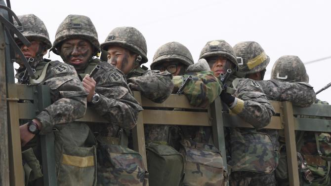 South Korean army soldiers on a military truck move during an exercise against possible attacks by North Korea in Pocheon, South Korea, near the border with North Korea, Monday, April 8, 2013. North Korea said Monday it will recall 51,000 North Korean workers and suspend operations at a factory complex it has jointly run with South Korea, moving closer to severing its last economic link with its rival as tensions escalate.(AP Photo/Ahn Yong-joon)