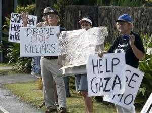 Protesters hold signs near Obama's vacation home in Hawaii