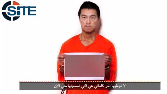 Image obtained from SITE Intelligence Group on January 24, 2015, shows Japanese hostage Kenji Goto in an orange blouse holding a photograph allegedly showing Haruna Yukawa's slain body