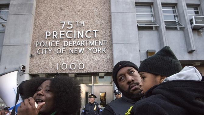 Protesters, demanding justice for Akai Gurley, turn their backs towards the New York Police Department's (NYPD) 75th Precinct after marching from the site of his shooting death in Brooklyn