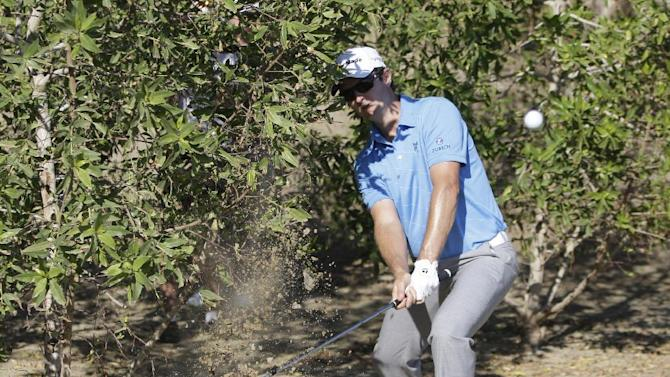 Justin Rose of England plays a ball in the bush of 14th hole during the third round of Abu Dhabi Golf Championship in Abu Dhabi, United Arab Emirates, Saturday, Jan. 19, 2013. (AP Photo/Kamran Jebreili)