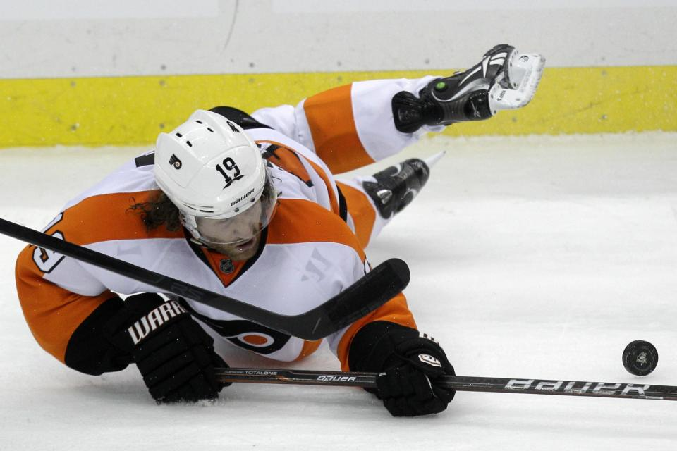 Philadelphia Flyers' Scott Hartnell (19) passes the puck as he falls to the ice during the third period of Game 1 in an opening-round NHL hockey playoff series against the Pittsburgh Penguins on Wednesday, April 11, 2012 in Pittsburgh. The Flyers won 4-3 in overtime. (AP Photo/Gene J. Puskar)