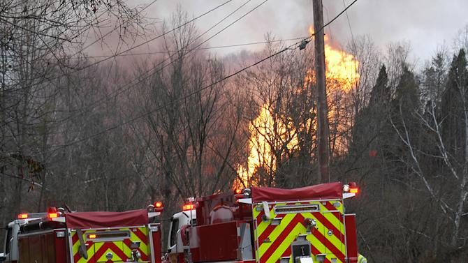 Firetrucks are ready as flames  from a gas line explosion riase near Sissonville, W.Va., Tuesday, Dec. 11, 2012. West Virginia State Police say several structures are on fire and about a mile of Interstate 77 is shut down in both directions.  (AP Photo/The Charleston Gazette/Rusty Marks)
