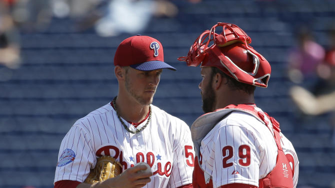 Philadelphia Phillies pitcher David Buchanan, left, talks with pitcher Cameron Rupp, right, in the first inning during a spring training baseball exhibition game against the New York Yankees, Tuesday, March 3, 2015, in Clearwater, Fla. (AP Photo/Lynne Sladky)