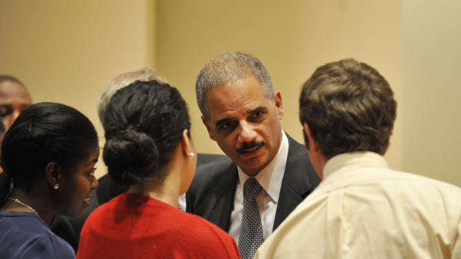 Attorney General Eric Holder, center, talks to a group of law students before delivering an address at the Northwestern University law school, Monday, March 5, 2012, in Chicago. (AP Photo/Brian Kersey)