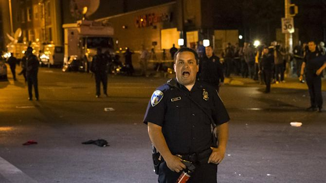 A police officer shouts towards residents to leave the intersection of North Ave and Pennsylvania Ave after a curfew in Baltimore