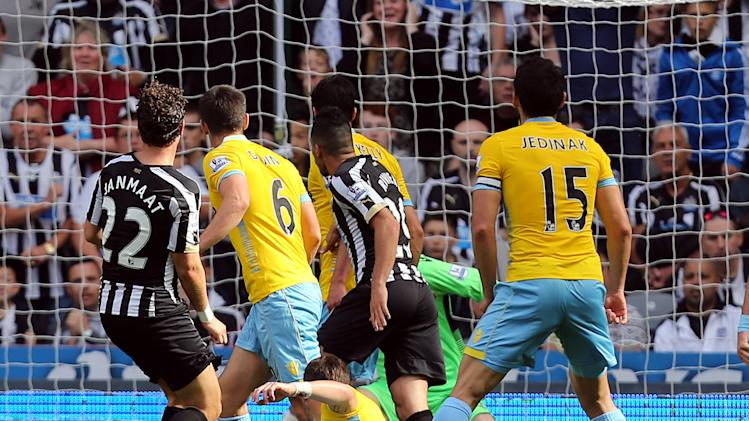 Newcastle United's Daryl Janmaat, left, scores his goal past Crystal Palace's Scott Dann, center, during their English Premier League soccer match at St James' Park, Newcastle, England, Saturday, Aug. 30, 2014. (AP Photo/Scott Heppell)