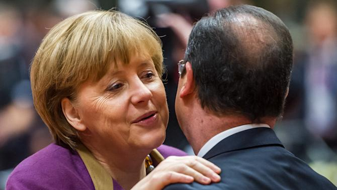 German Chancellor Angela Merkel, left, greets French President Francois Hollande during a round table meeting at an EU summit in Brussels on Friday, March 15, 2013. On the second anniversary of an uprising that evolved into Syria's brutal civil war, the European Union's national leaders will likely discuss whether to arm rebels trying to overthrow the regime of Bashar Assad. (AP Photo/Geert Vanden Wijngaert)