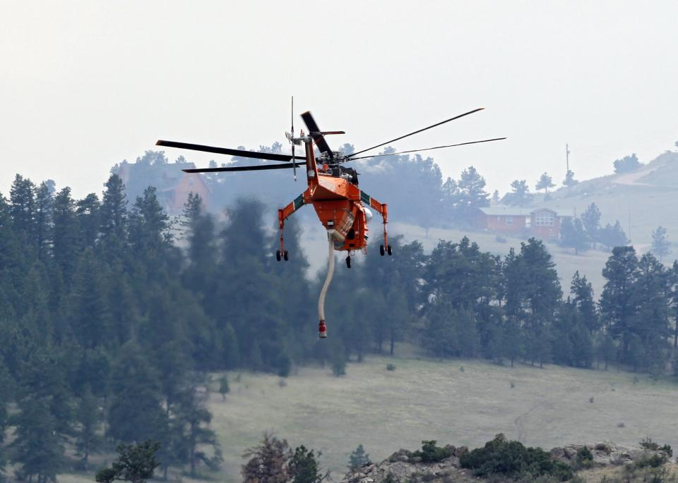A helicopter lifts off after taking on water to drop on the High Park Fire west of Fort Collins, Colo., on Monday,  June 18, 2012. The wildfire has now burned about 90 square miles and destroyed more than 180 homes.  (AP Photo/Ed Andrieski)