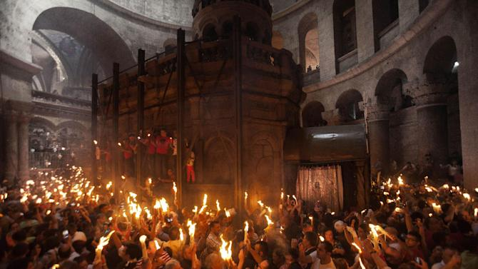 """Christian pilgrims hold candles at the church of the Holy Sepulcher, traditionally believed to be the burial site of Jesus Christ, during the ceremony of the Holy Fire in Jerusalem's Old City, Saturday, April 19, 2014. The """"holy fire"""" was passed among worshippers outside the Church and then taken to the Church of the Nativity in the West Bank town of Bethlehem, where tradition holds Jesus was born, and from there to other Christian communities in Israel and the West Bank. (AP Photo/Dan Balilty)"""